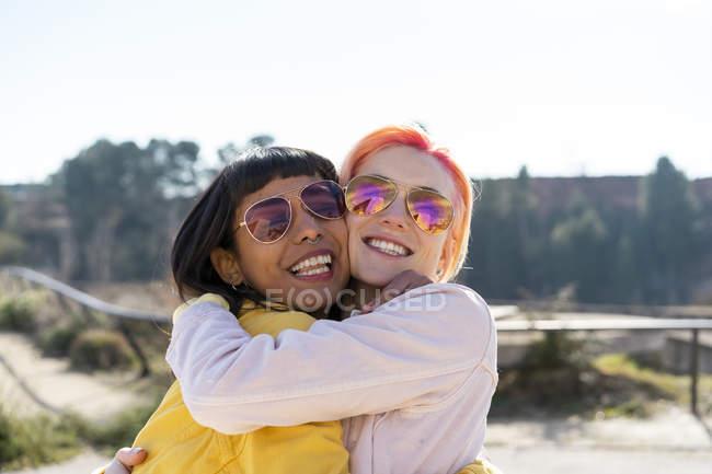 Retrato de dos amigos alternativos abrazando - foto de stock