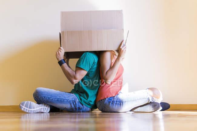 Пара с головами в картонной коробке сидя спиной к спине на полу в новом доме — стоковое фото
