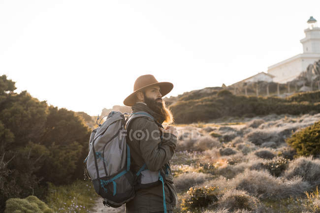 Italy, Sardinia, hiker with hat and backpack watching something — Stock Photo