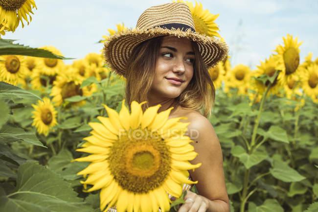 Молодая женщина в соломенной шляпе улыбается в поле подсолнухов — стоковое фото