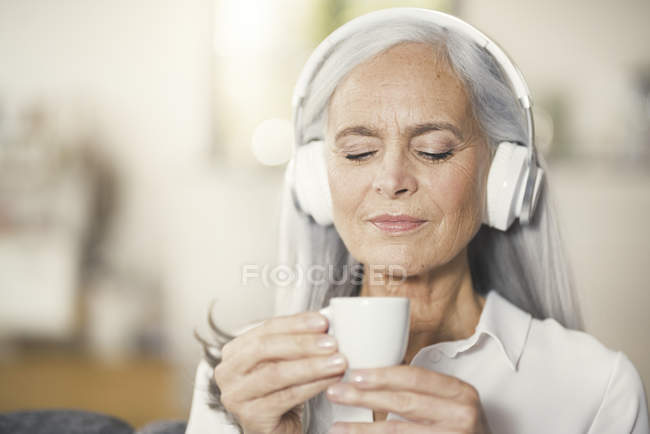 Senior woman listen music with headphones and drinking coffee — Stock Photo