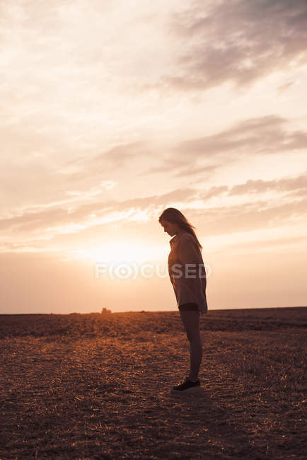 Lonely young woman standing on field at sunset — Stock Photo
