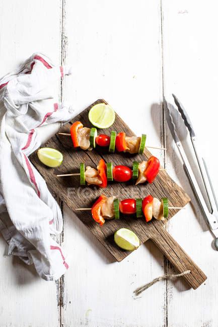 Гриль шампуры с сырой курицей, помидорами, болгарским перцем и цуккини на разделочной доске — стоковое фото