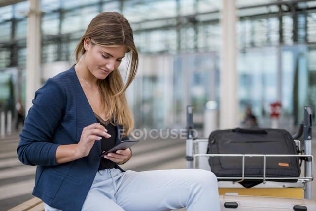 Giovane donna d'affari sorridente seduta all'aperto con cellulare e valigia — Foto stock