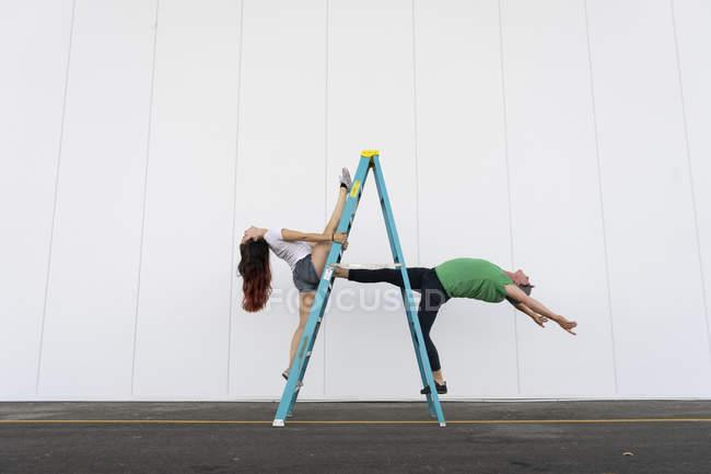 Deux acrobates faisant des tours sur une échelle — Photo de stock