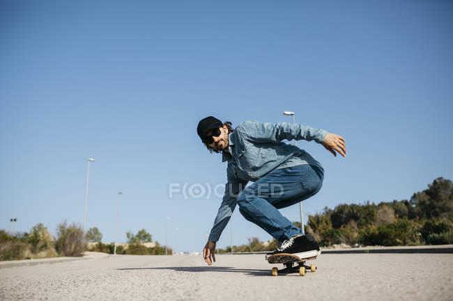 Uomo alla moda in denim e berretto skateboard su strada — Foto stock