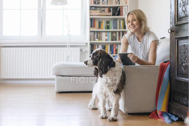 Femme mûre souriante avec chien couché sur le canapé à la maison et tenant la tablette — Photo de stock