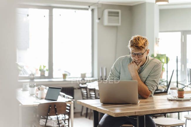 Young man sitting in coffee shop and using laptop — Stock Photo
