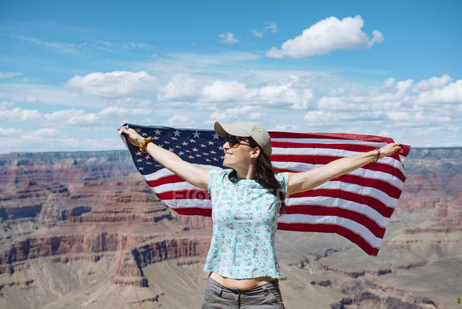 USA, Arizona, smiling woman with American flag at Grand Canyon National Park — Stock Photo