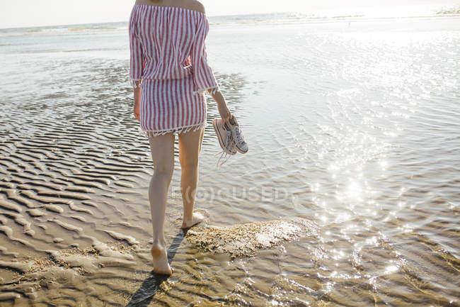 Vista posteriore della donna che trasporta scarpe e cammina sulla spiaggia sabbiosa in acqua di mare — Foto stock