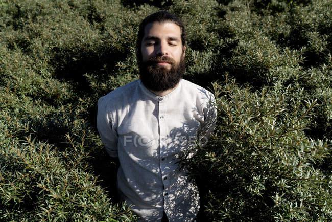 Jovem de pé em arbustos, desfrutando do sol — Fotografia de Stock