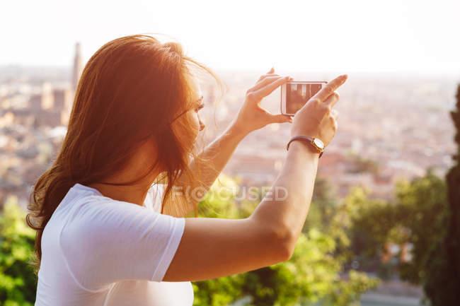 Италия, Верона, Италия, Верона, рыжая женщина, фотографирующаяся со смартфоном на закате — стоковое фото