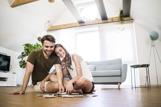 Happy couple sitting on floor at home looking at ultrasound scans — Stock Photo
