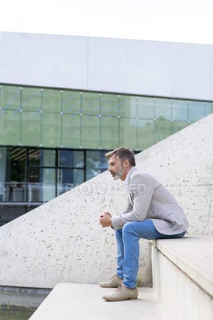 Uomo d'affari pensieroso seduto su gradini all'aperto — Foto stock