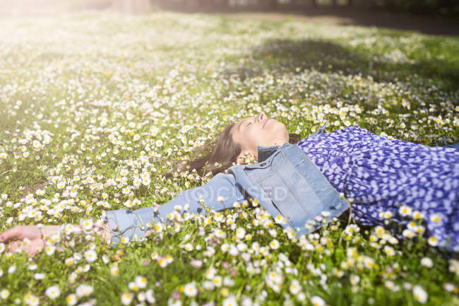 Relaxed young woman lying on flower meadow in park — Stock Photo