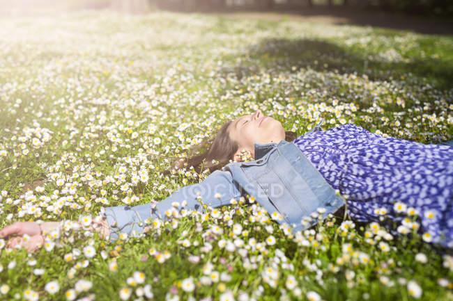 Giovane donna rilassata sdraiata sul prato di fiori nel parco — Foto stock