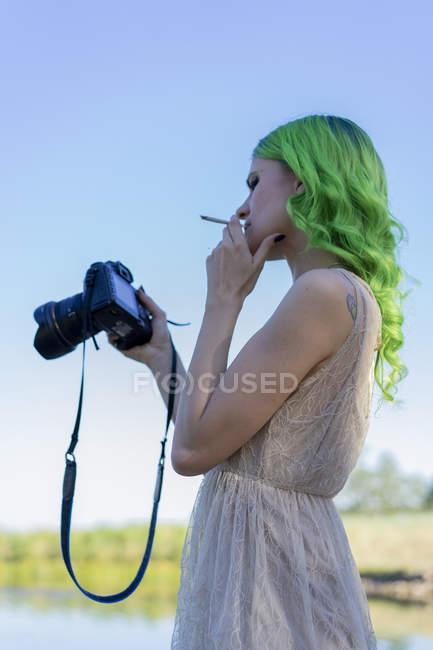 Молодая женщина с окрашенными зелеными волосами курит сигарету в природе, глядя на дисплей цифровой камеры — стоковое фото