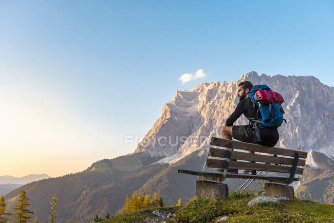 Austria, Tyrol, Hiker taking a break, sitting on bench, looking at view — Stock Photo