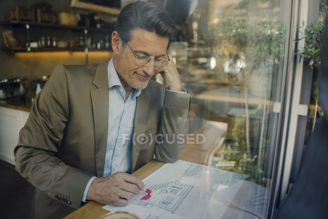 Mature businessman sitting in coffee shop, drawing outline of a house — Stock Photo