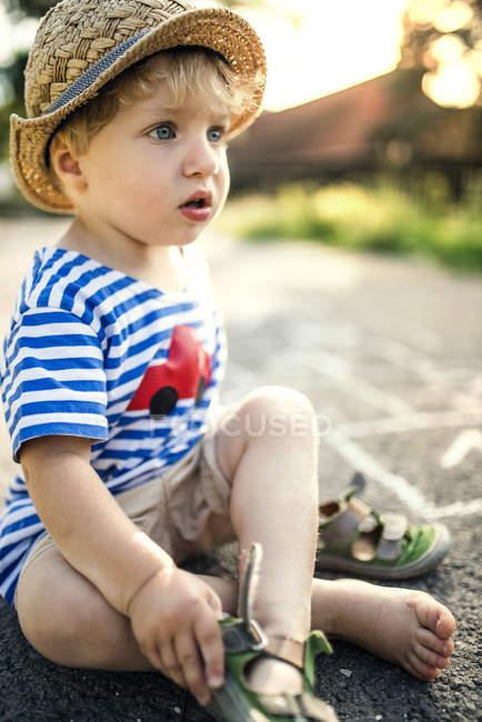 Retrato del niño sentado en la calle quitándose los zapatos - foto de stock