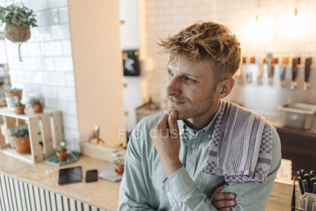 Young man working in his start-up cafe, thinking — Stock Photo