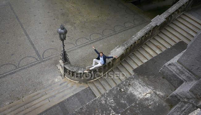 Deutschland, München, Geschäftsmann mit erhobenen Armen am Geländer — Stockfoto