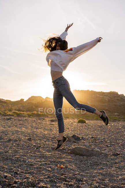 Giovane donna in spiaggia, che balla al tramonto — Foto stock