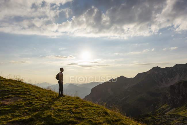 Человек, стоящий в горах — стоковое фото