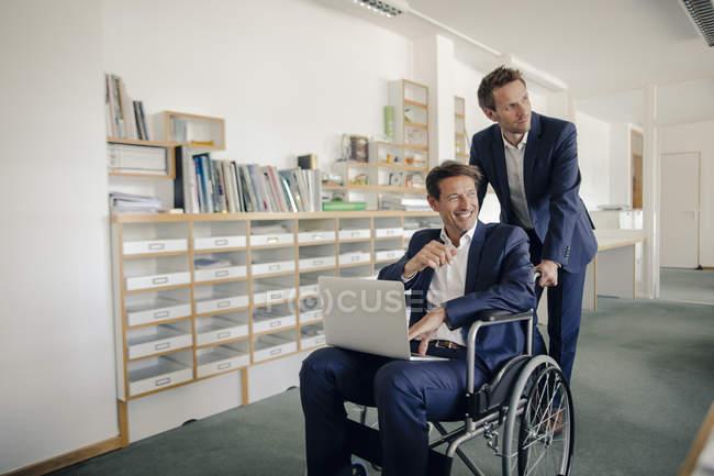 Коллега толкает бизнесмена, сидящего в колесном колесе?r — стоковое фото