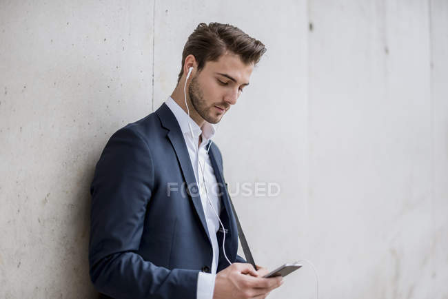 Businessman with earbuds and cell phone leaning against a wall — Stock Photo