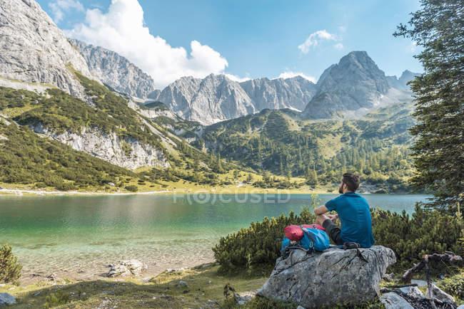Austria, Tirolo, Escursionista in pausa, seduto sulla roccia, guardando il lago — Foto stock