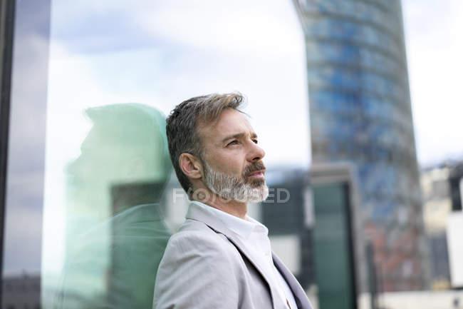 Spain, Barcelona, pensive businessman leaning against glass facade — Stock Photo