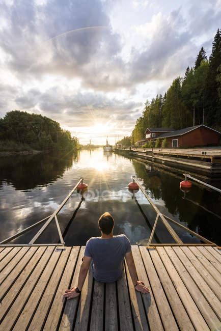 Финляндия, Каяани, Человек, сидящий на причале, наблюдая закат, вид сзади — стоковое фото