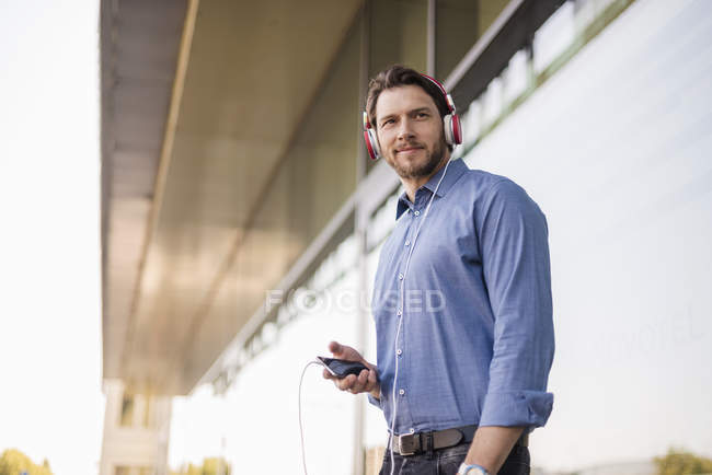 Smiling man listening to music with headphones outdoors — Stock Photo