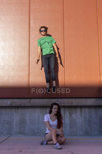 Acrobata que salta meados de-ar atrás da mulher de assento, olhando triste — Fotografia de Stock
