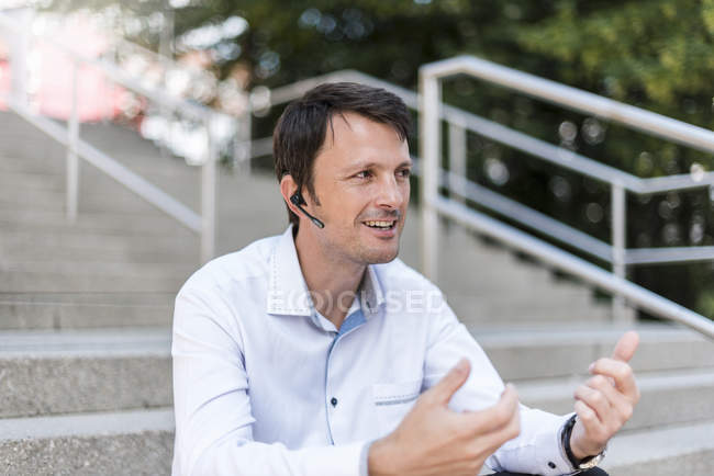 Smiling businessman with headset sitting on stairs — Stock Photo