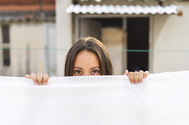Porträt einer jungen Frau hinter trocknenden Bettlaken auf der Dachterrasse — Stockfoto