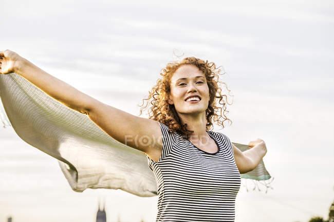 Retrato da mulher nova feliz com os braços outstretched o lenço da terra arrendada — Fotografia de Stock