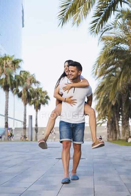 Happy couple in city, man carrying girlfriend piggyback — стокове фото