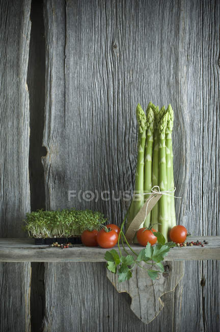 Bundle of white asparagus, tomatoes, parsley and mixed pepper on wood — Stock Photo
