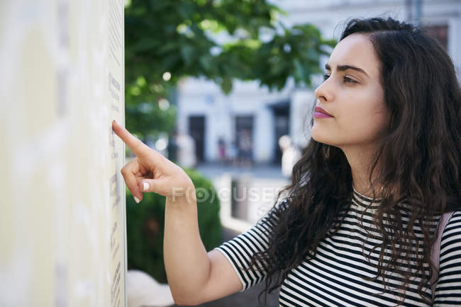 Young woman checking timetable of public transport — Stock Photo