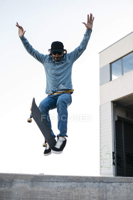 Trendy man in denim and cap skateboarding, doing jump with skateboard from concrete ramp — Stock Photo