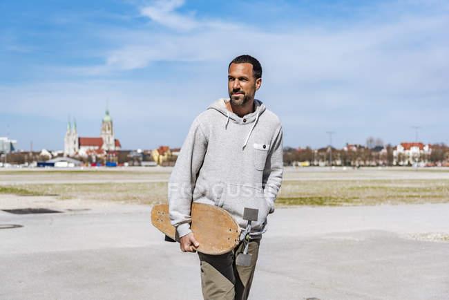 Mann trägt Longboard im Freien — Stockfoto