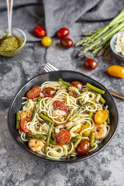 Spaghetti aux crevettes, asperges vertes, tomates, pesto et parmesan — Photo de stock