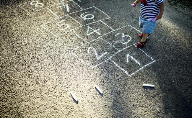 Маленькая девочка с нарисованным классическим рисунком на улице, частичный вид — стоковое фото