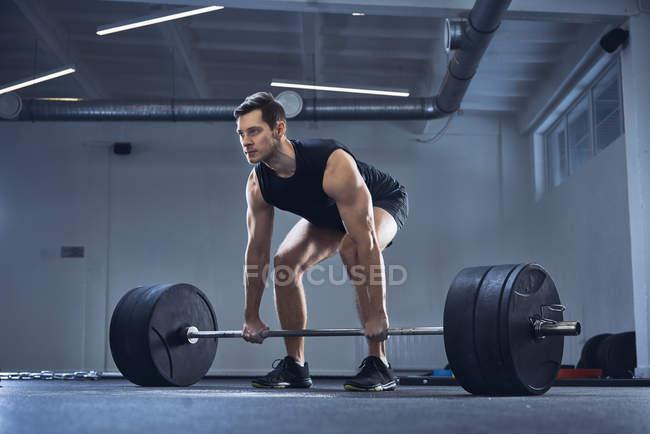 Homme faisant l'exercice d'haltère à la salle de gym pendant l'entraînement de levage de poids — Photo de stock