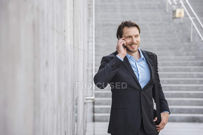Smiling businessman at stairs talking on smartphone — Stock Photo