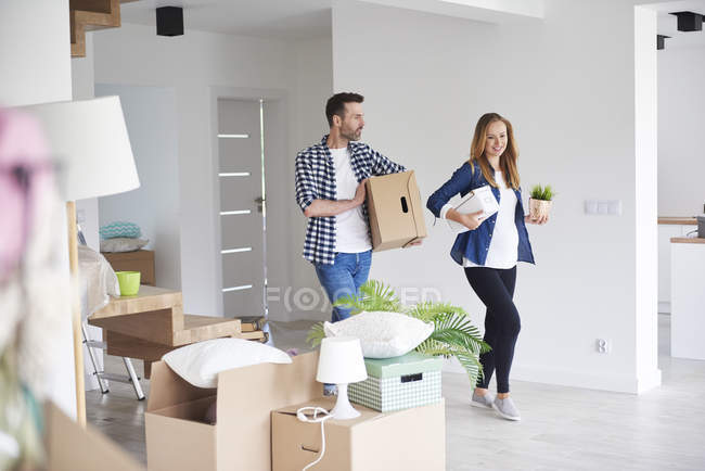 Couple moving into new flat carrying cardboard box and plant — Stock Photo