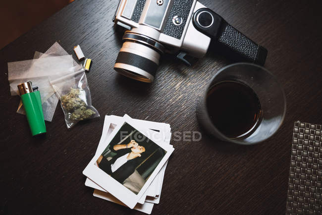 Marihuana, cigarette lighter, glass, polaroids and analog camera on wooden surface - foto de stock