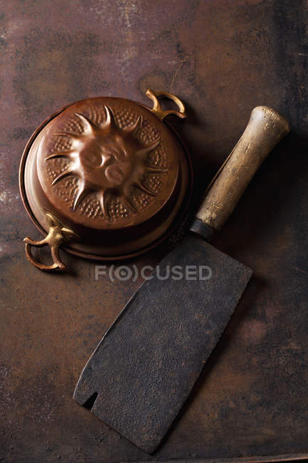 Old copper baking dish and cleaver on rusty ground — Stock Photo
